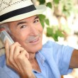 Older man using a cell phone outdoors — Stock Photo #10511529