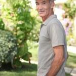 Senior man walking in the garden — Stock Photo #10511657