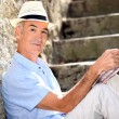 Stock Photo: Retired mreading his guidebook