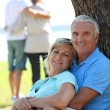 Mature couple leaning on tree trunk — Stock Photo