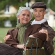 Royalty-Free Stock Photo: Elderly couple sat on a park bench