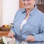 Senior woman preparing salad — Stock Photo