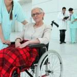 Nurse with elderly invalid — Stock Photo