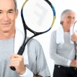 Senior couple with tennis rackets — Stock Photo