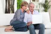 Mature couple on sofa with computer — Stock Photo