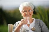Mulher sênior com um copo de água — Foto Stock