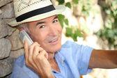 Starší muž pomocí mobilní telefon venku — Stock fotografie