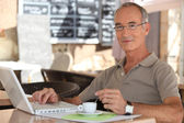 Grey-haired man in coffee shop — Stock Photo