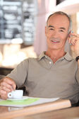 Retired man drinking coffee — Stock Photo