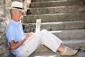 Senior gentleman working on laptop outdoors — Stock Photo