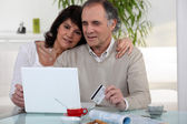 Middle-aged couple shopping on-line — Stock Photo