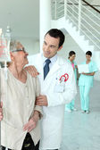 Doctor with senior woman in hospital — Stock Photo