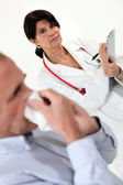 Doctor writing on a clipboard as her patient blows his nose — Stock Photo