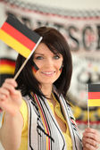 Germany supporter holding miniature flags — Stock Photo
