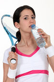 A tenniswoman taking a sip of water. — Stock Photo