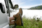 Man snoozing in car parked by lake — Stockfoto
