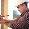 Carpenter marking wooden panel — Stock Photo