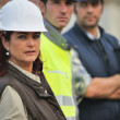 Three construction colleagues stood in a row — Stock Photo #10520584