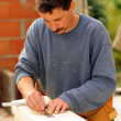 Stock Photo: Carpenter marking wood with pencil