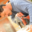 Stock Photo: Experienced manual worker using circular saw