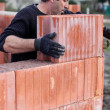 Mason placing brick on unfinished wall — Stock Photo