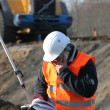 Surveyor working on construction site - Stock Photo