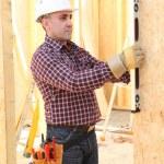 Man using spirit-level on wooden panel — Stock Photo