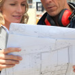 Female architect and workman consulting blueprints in construction site — Stock Photo #10521595