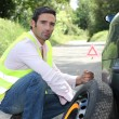 Stock Photo: Mchanging tyre at side of road