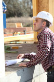 Foreman inspecting progress of wooden house — Stock Photo