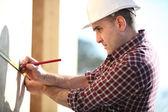 Carpenter marking wooden panel — Stock Photo