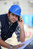 Foreman checking plans whilst on the phone — Stock Photo