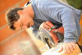 Experienced manual worker using circular saw — Stock Photo