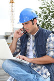 Construction worker with computer and phone — Stock Photo