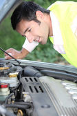 Man looking at a car engine — Stock Photo