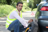 Man changing a tyre at the side of the road — Stock Photo
