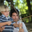 A man and a little boy doing archery in the forest — Stock Photo #8009988