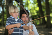 A man and a little boy doing archery in the forest — Stock Photo