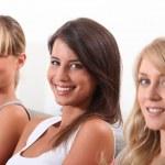 Three pretty young women sitting on a sofa — Stock Photo