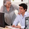 Young man using computer and happy senior woman — Stock Photo