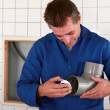 Stock Photo: Plumber fastening piece