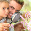 Father and little daughter observing flowers with magnifying glass — Stock Photo