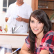 Young woman sitting at the kitchen table doing paperwork while her boyfrien — Stock fotografie