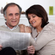 Stock Photo: Couple reading newspaper together