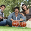 Musical trio in green setting — Stock Photo
