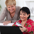 Two middle aged women online shopping. — Stock Photo