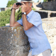 Man with binoculars and a hat — Stock Photo #8013872