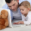 Young girl playing with her father's laptop - Stock Photo