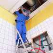 Stock Photo: Plumber working on ladder