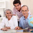 Young man and senior couple seeking a route on a map — Stock Photo #8014283